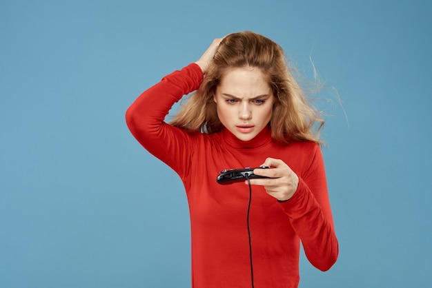 Une femme joue à un jeu d'ordinateur dans des consoles avec des joysticks