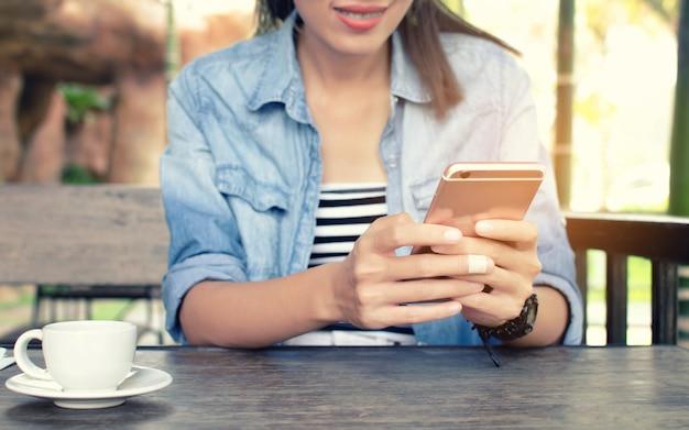 Femme jouer au smartphone dans un café