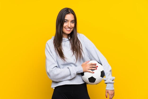 Femme de joueur de football jeune sur mur jaune isolé