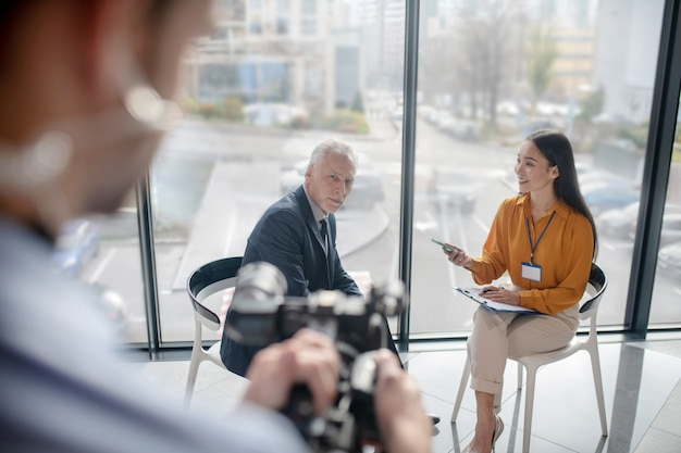 Femme journaliste asiatique implantation dans le studio interviewant un homme d'affaires célèbre