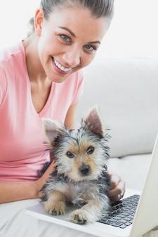 Femme joyeuse à l'aide d'ordinateur portable avec son yorkshire terrier
