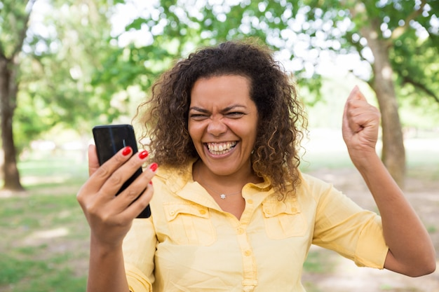 Femme joyeuse à l'aide de smartphone dans le parc de la ville