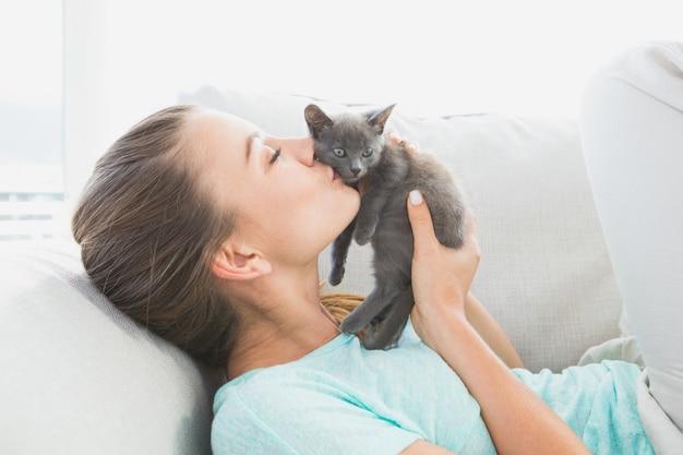 Femme joyeuse allongée sur le canapé en train d'embrasser un chaton gris