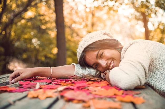 Femme joyeuse allongée sur une table avec des feuilles d'automne