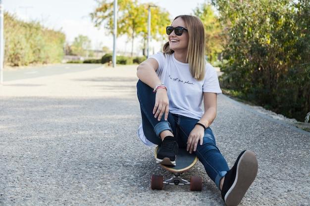 Femme joyeuse, assis sur le longboard