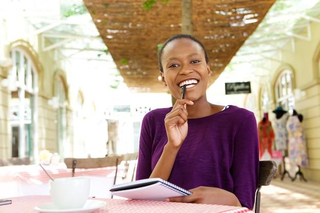 Femme joyeuse au café, prendre des notes