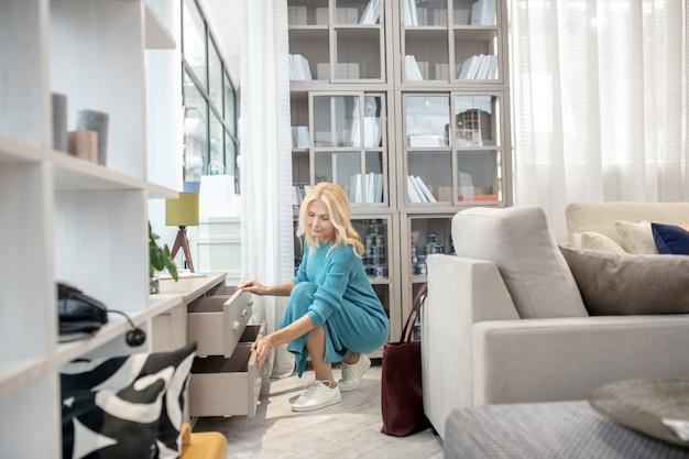 Femme joyeuse aux cheveux blonds sur les épaules, accroupie en regardant les tiroirs allongés d'une nouvelle armoire dans le salon de meubles.