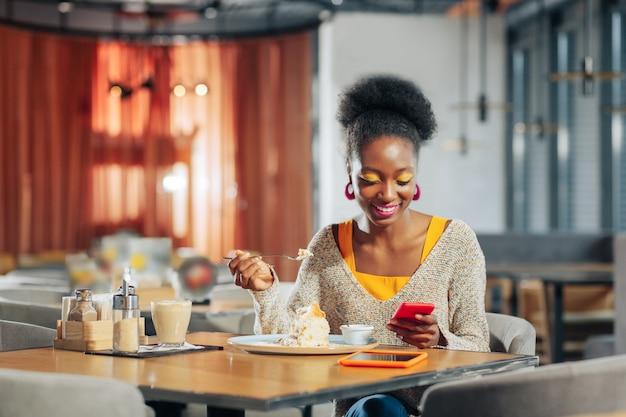 Femme joyeuse aux cheveux noirs bouclés lisant un message sur un smartphone