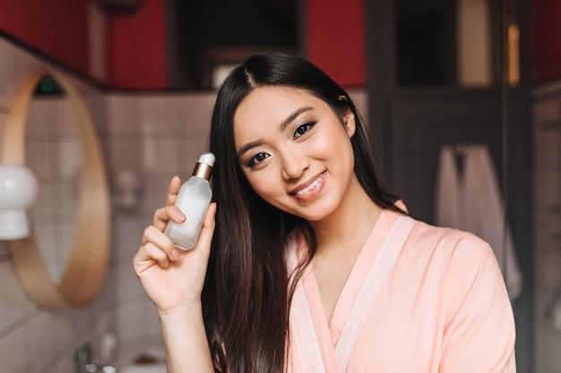 Femme joyeuse aux yeux bruns détient une émulsion pour le visage et pose dans la salle de bain