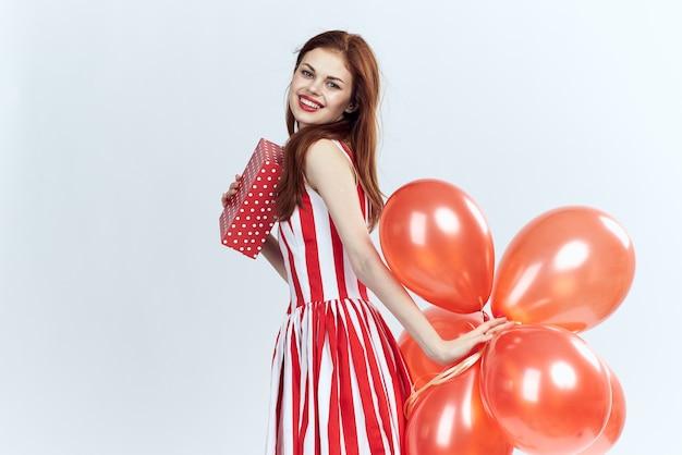 Femme joyeuse avec des ballons rouges et une robe rayée sur blanc