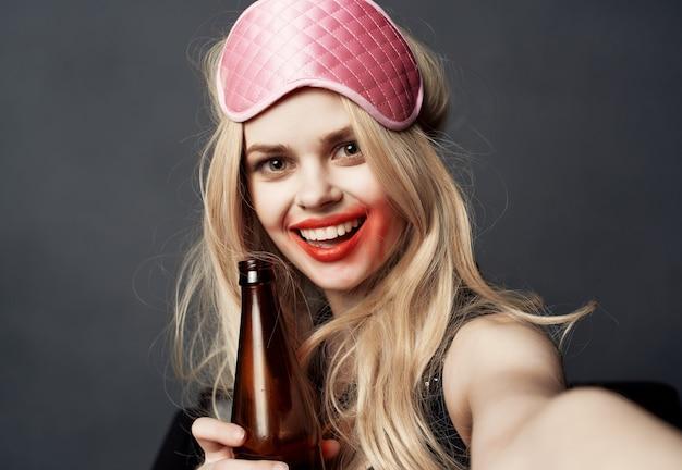 Femme joyeuse barbouillé de rouge à lèvres vie nocturne bouteille d'alcool fond sombre