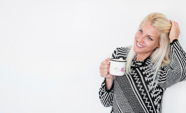Femme joyeuse avec une boisson chaude touchant les cheveux