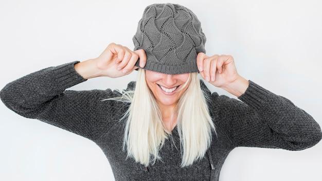 Femme joyeuse cachant le visage derrière le chapeau