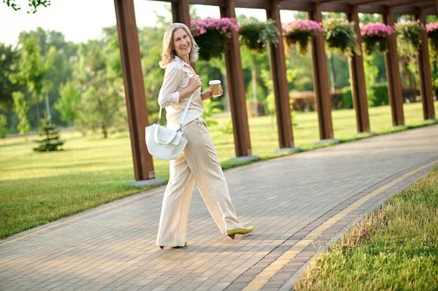 Femme joyeuse avec café marchant dans le parc