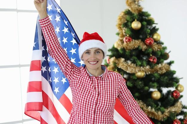 Une femme joyeuse en chapeau de père noël tient le drapeau de l'amérique sur fond d'arbre du nouvel an