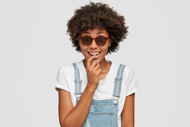 Une femme joyeuse a une coiffure afro bouclée et touffue, sourit positivement