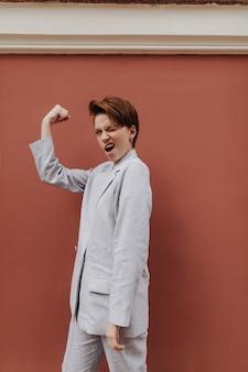 Femme joyeuse en costume gris montrant sa puissance. fille aux cheveux courts en veste et pantalon surdimensionnés démontre les biceps sur isolé