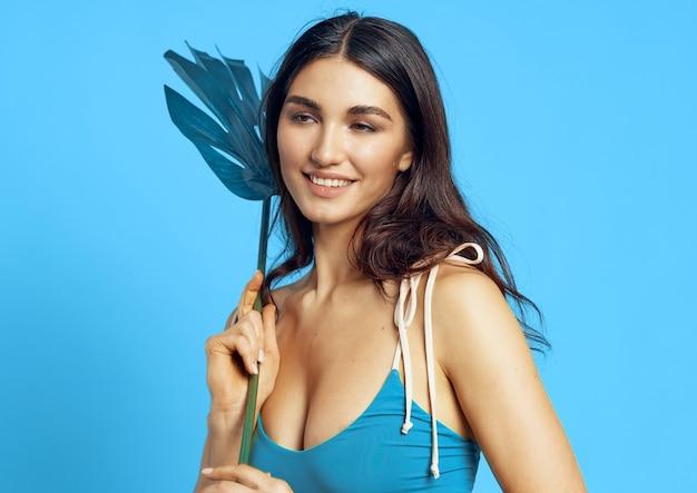Femme joyeuse dans un maillot de bain bleu feuille de palmier fond bleu exotique