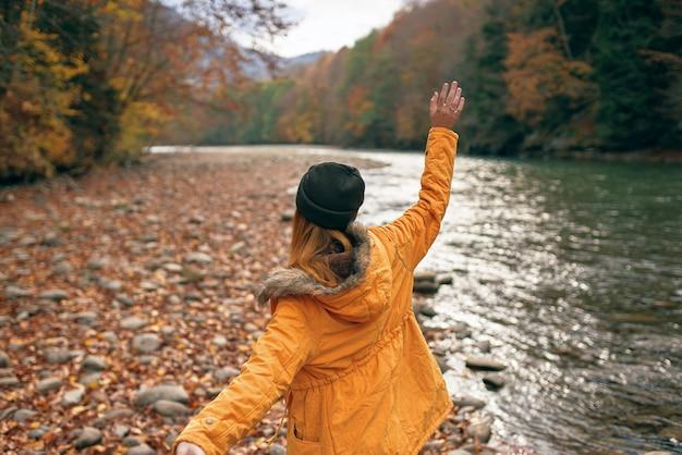 Femme joyeuse dans la nature forêt d'automne rivière