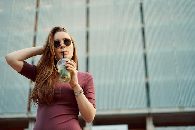Femme joyeuse dans la rue, boire une boisson rafraîchissante le matin