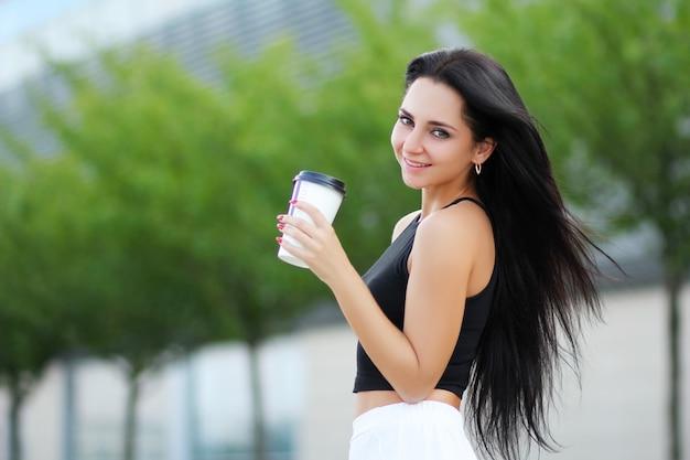 Femme joyeuse dans la rue en buvant un café au soleil