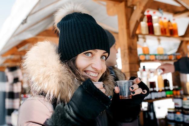 Femme joyeuse dans des vêtements d'hiver chauds au marché, essayez des boissons