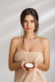 Femme joyeuse debout dans une serviette, tenant un gommage corporel, regardant droit.