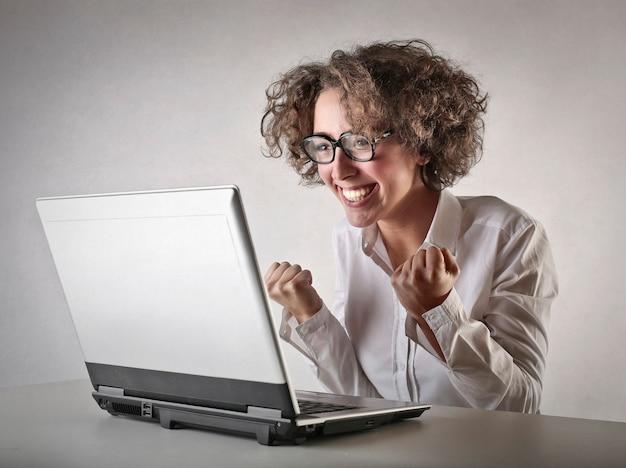 Femme joyeuse devant un ordinateur portable