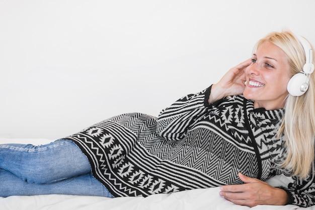 Femme joyeuse écoutant de la musique sur le lit