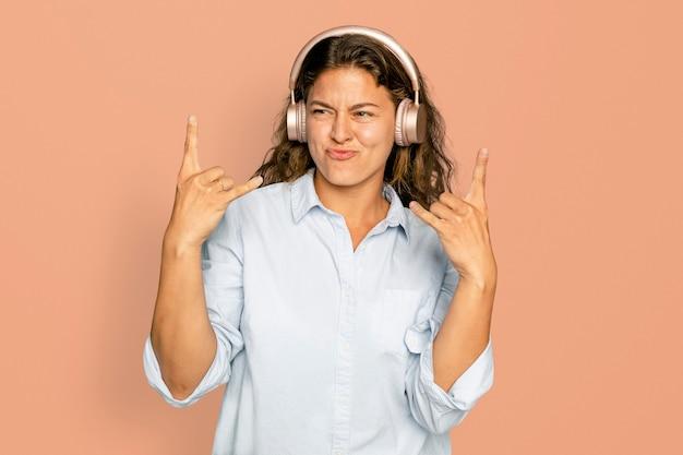 Femme joyeuse écoutant de la musique via un appareil numérique d'écouteurs