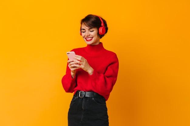 Femme joyeuse écoute de la musique et regarde le smartphone