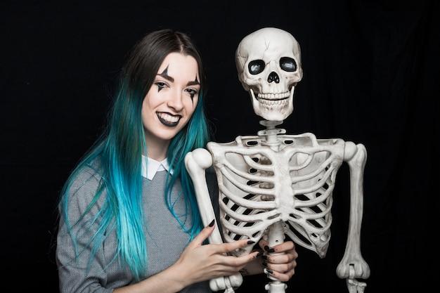 Femme joyeuse embrassant le squelette