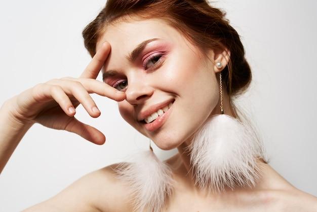 Femme joyeuse épaules nues boucles d'oreilles moelleuses maquillage lumineux agrandi.