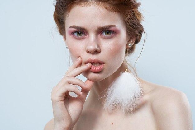 Femme joyeuse épaules nues boucles d'oreilles moelleuses studio vue recadrée. photo de haute qualité