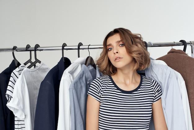 Femme joyeuse essayant sur fond isolé de magasin de vêtements au détail. photo de haute qualité
