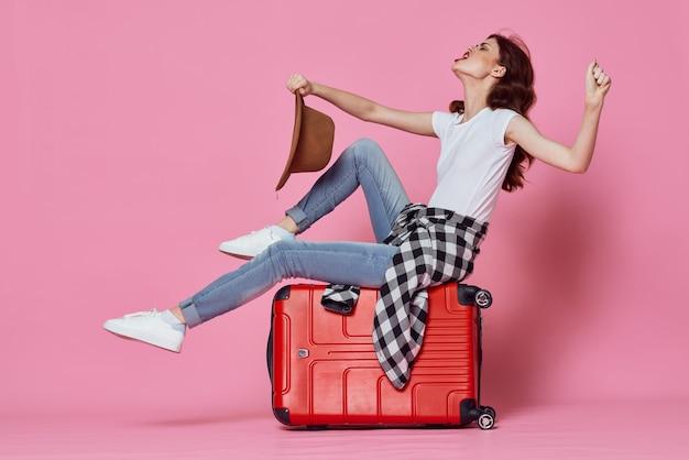 Une femme joyeuse est assise sur un aéroport de vol de valise rouge