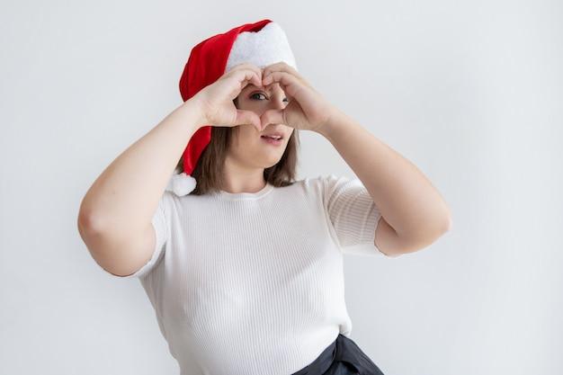 Femme joyeuse faisant un geste du coeur et regardant la caméra