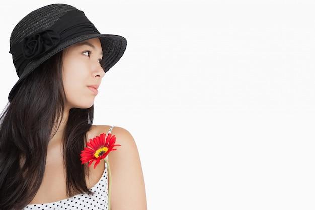 Femme joyeuse avec fleur regardant loin portant un chapeau