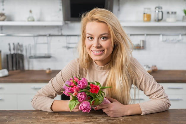Femme joyeuse avec des fleurs fraîches dans la cuisine