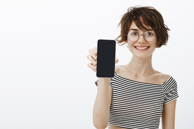Femme joyeuse hipster présente l'application, montrant l'écran du smartphone