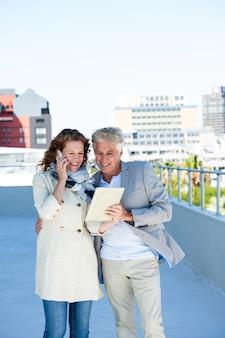 Femme joyeuse avec homme à l'aide de tablette numérique