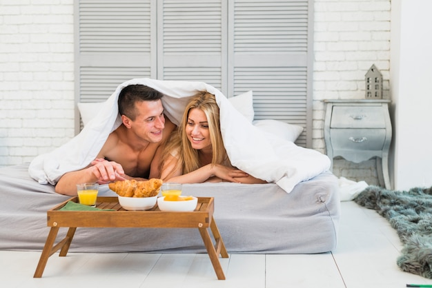 Femme joyeuse et jeune homme au lit sous la couverture près de la nourriture sur la table du petit déjeuner dans la chambre