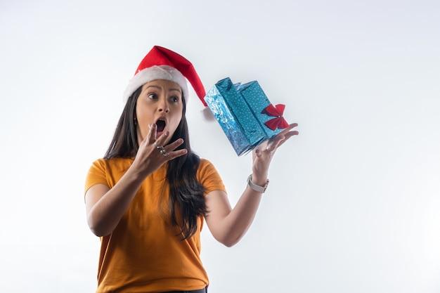 Femme joyeuse latine avec boîte de cadeaux volants. fond blanc