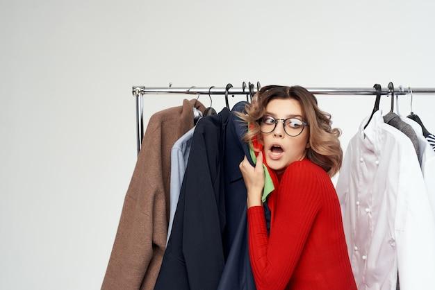 Femme joyeuse avec des lunettes à côté de vêtements mode émotions amusantes. photo de haute qualité