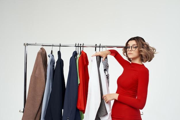 Femme joyeuse avec des lunettes à côté de vêtements mode fun fond clair