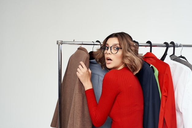 Femme joyeuse avec des lunettes essayant sur fond clair accro du shopping magasin de vêtements