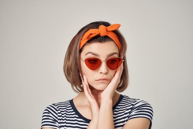 Femme joyeuse à lunettes de soleil avec un bandage sur la tête posant à la mode