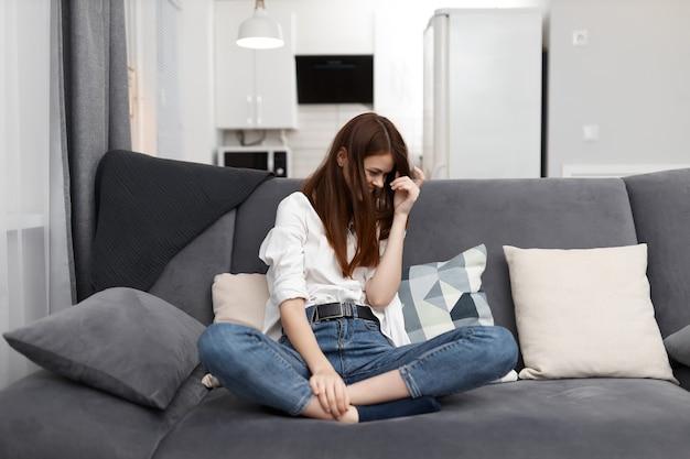 Femme joyeuse à la maison sur le canapé reste confort dans l'appartement