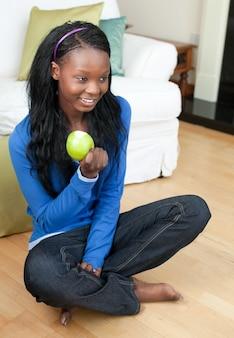 Femme joyeuse mange une pomme assis sur le sol