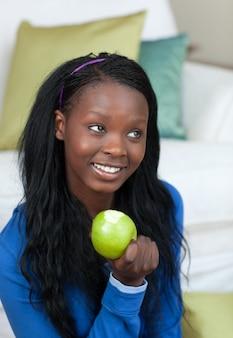 Femme joyeuse mange une pomme